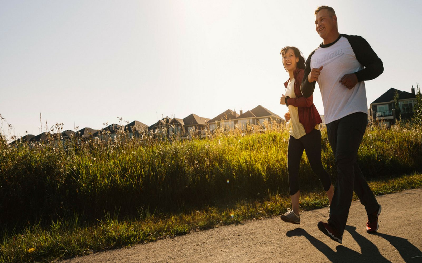 couple-running-in-cranstons-riverstone-calgary-alberta