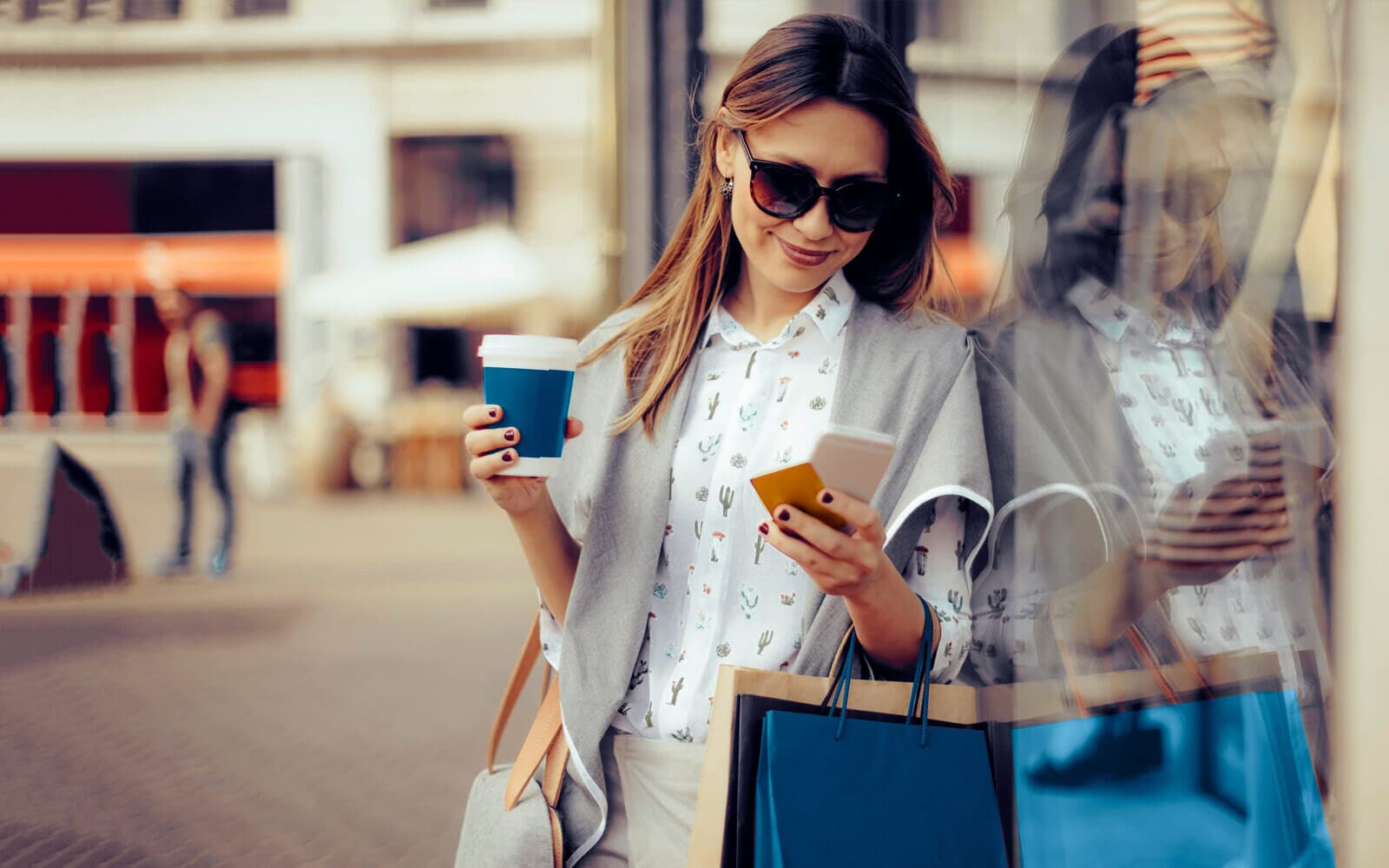 Woman on her phone, holding a to-go cup of coffee and shopping bags