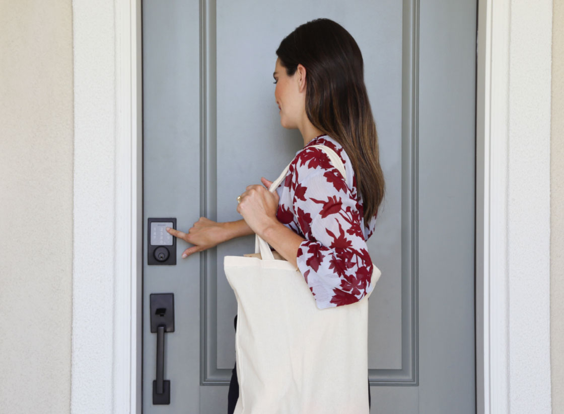 Woman entering a code on a front door smart lock keypad
