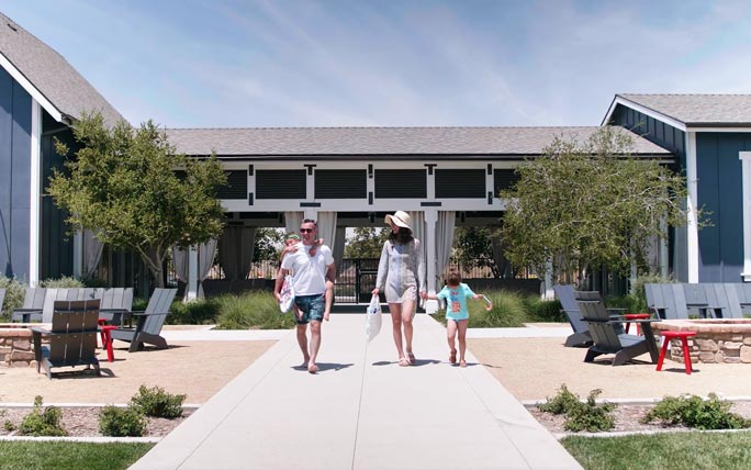 Family walking in front of the Ranch House in Audie Murphy Ranch in Menifee, CA | Brookfield Residential