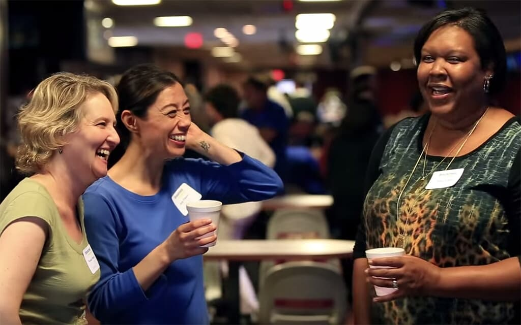People socializing and laughing at an event | Brookfield Residential