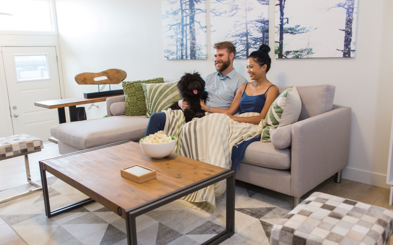 Couple Relaxing with Dog on the Couch | Vista Pointe at Chappelle Gardens | Edmonton, Alberta | Brookfield Residential