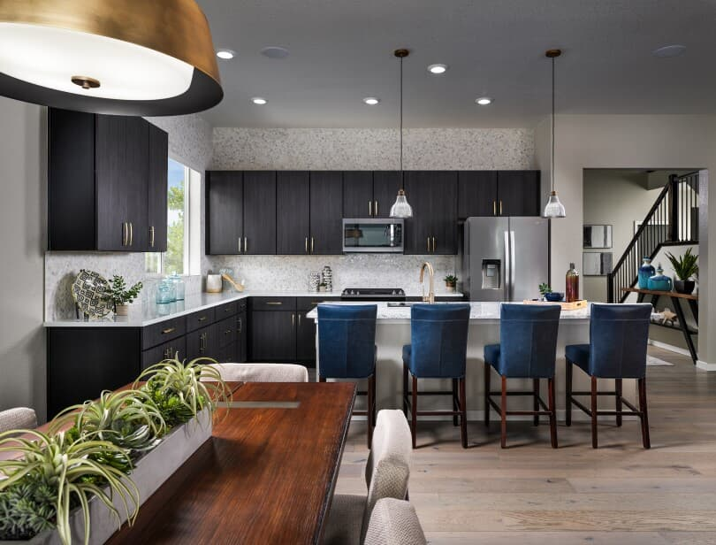 Kitchen table with chairs, breakfast bar with blue chairs in an Ovation Portfolio home