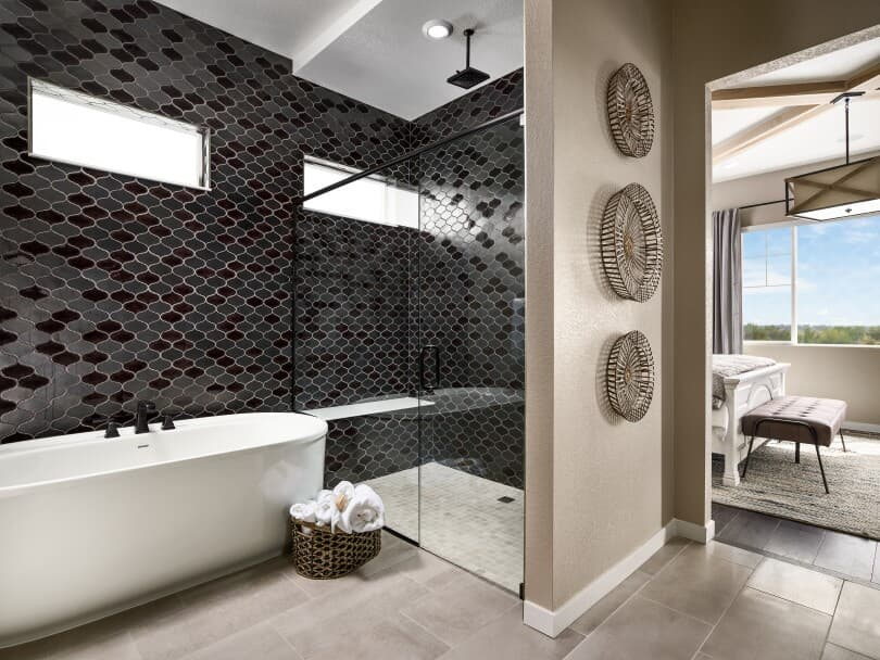 Spa-style bathroom with tub and overhead shower in an Ovation Portfolio home