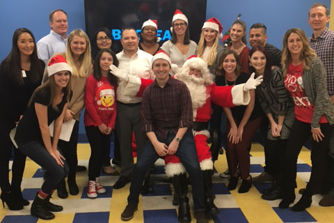 Brookfield employees posing with Santa Claus at the Boy and Girls Club in Anaheim, California