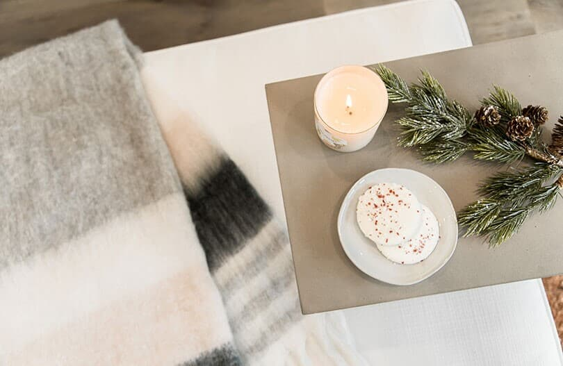 Cozy setting with a blanket, candle, and cookies in a Brookfield Residential home