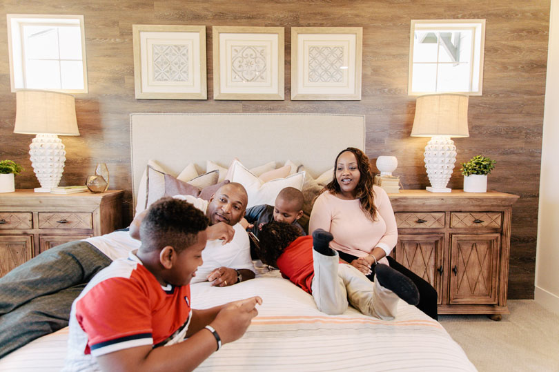 A family sitting on a bed in a designer furnished bedroom