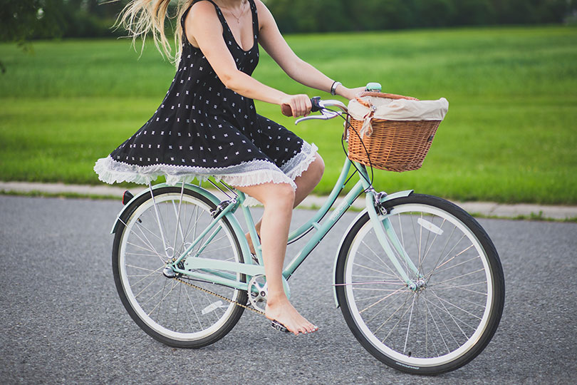Girl in dress riding bike barefoot