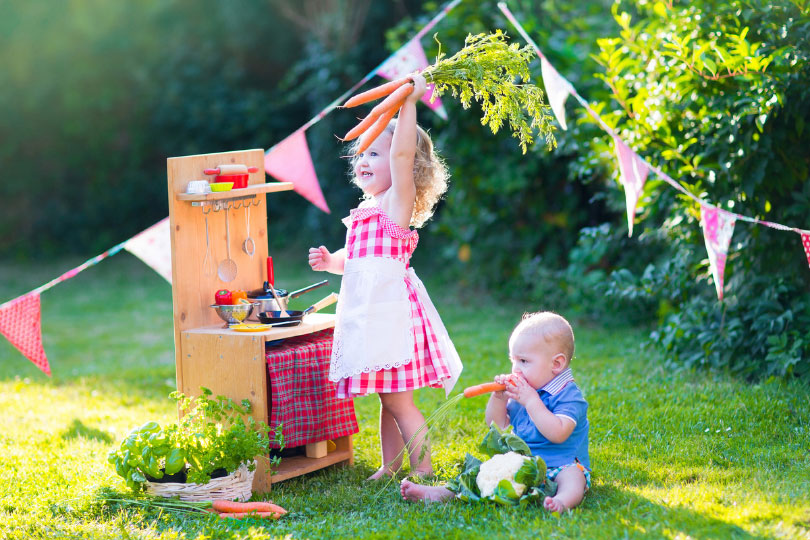 Girl and baby playing house on a backyard