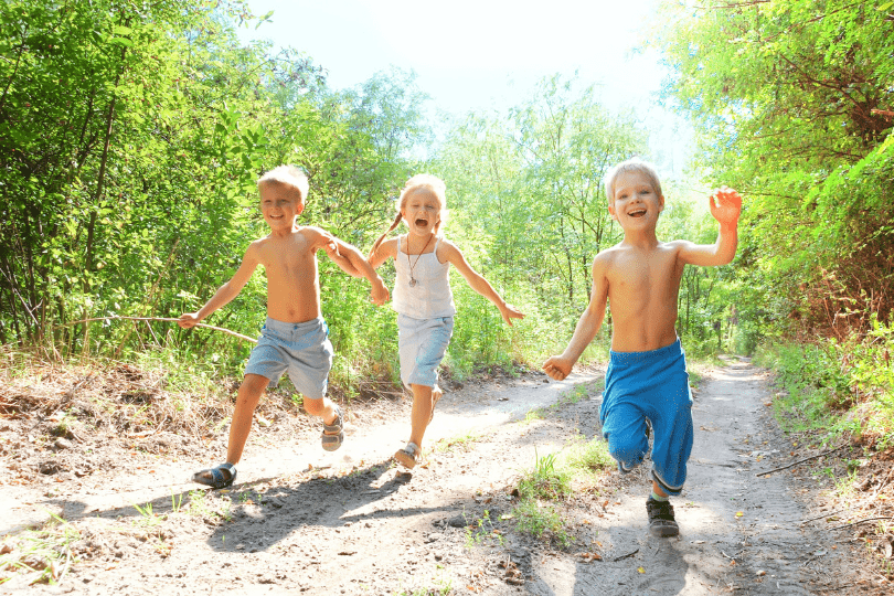 Kids running on forest pathway in the summertime
