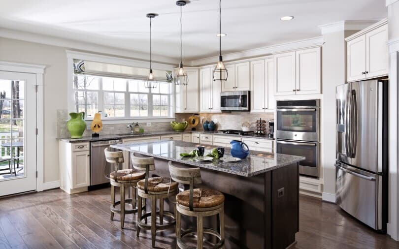 White kitchen with dark island in Beckner at Two Rivers in Odenton, MD