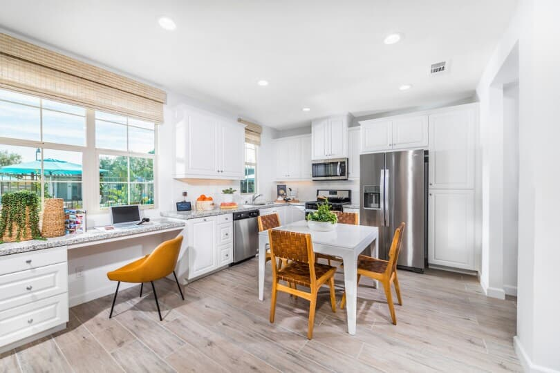 Bright white kitchen and tech space at Lantana@Beach Towns in Stanton, CA by Brookfield Residential