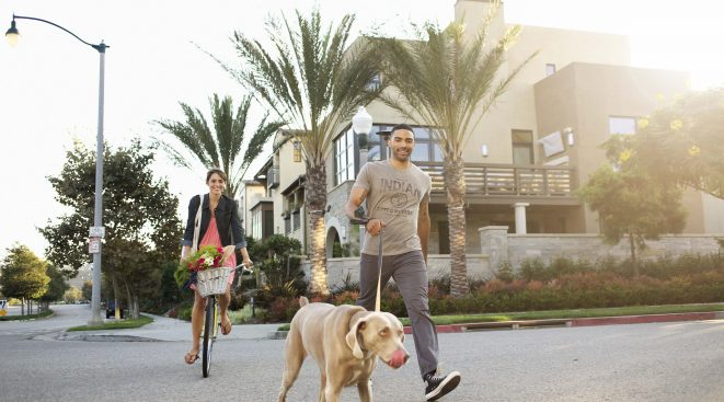 Man walking a dog and woman biking within Playa Vista community in Los Angeles, CA | Brookfield Residential