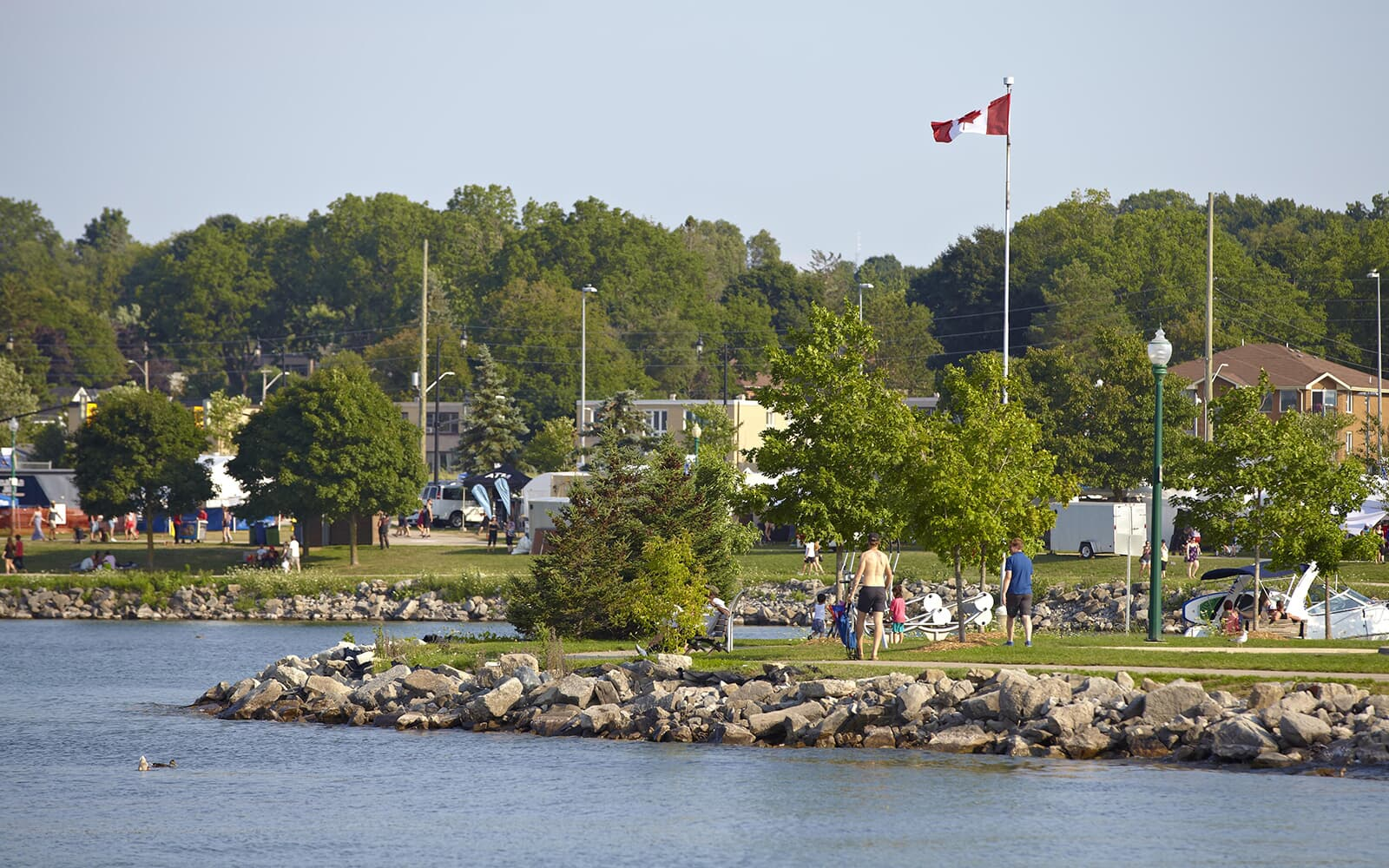 Lakeside Park with People and Canada Flag in Baxter, Ontario.
