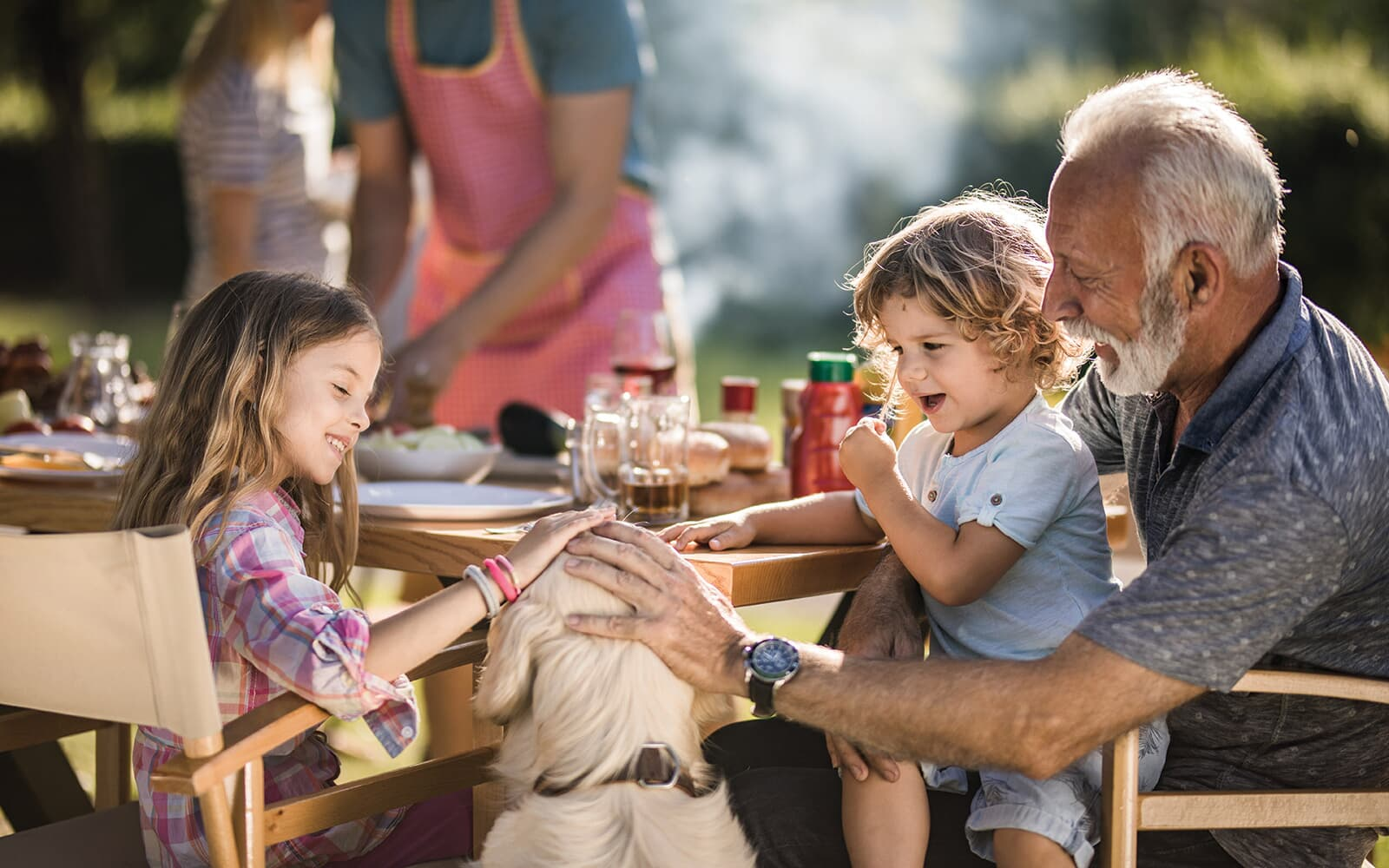 Grandfather With Grandaughters Petting a Dog at Family BBQ