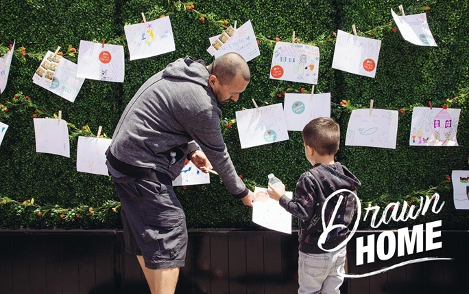 Father helps son hang his drawing  | Brookfield Residential Drawn Home