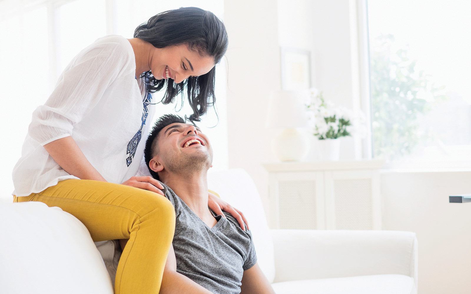 Couple sitting on a couch, smiling while looking at each other