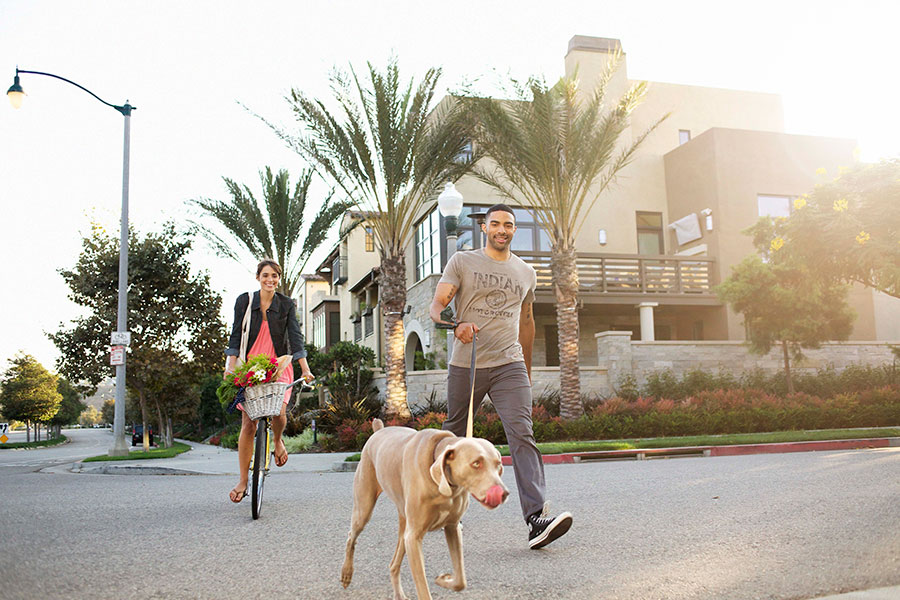 Guy walking dog and woman on bicycle at Playa Vista in Los Angeles CA Brookfield Residential