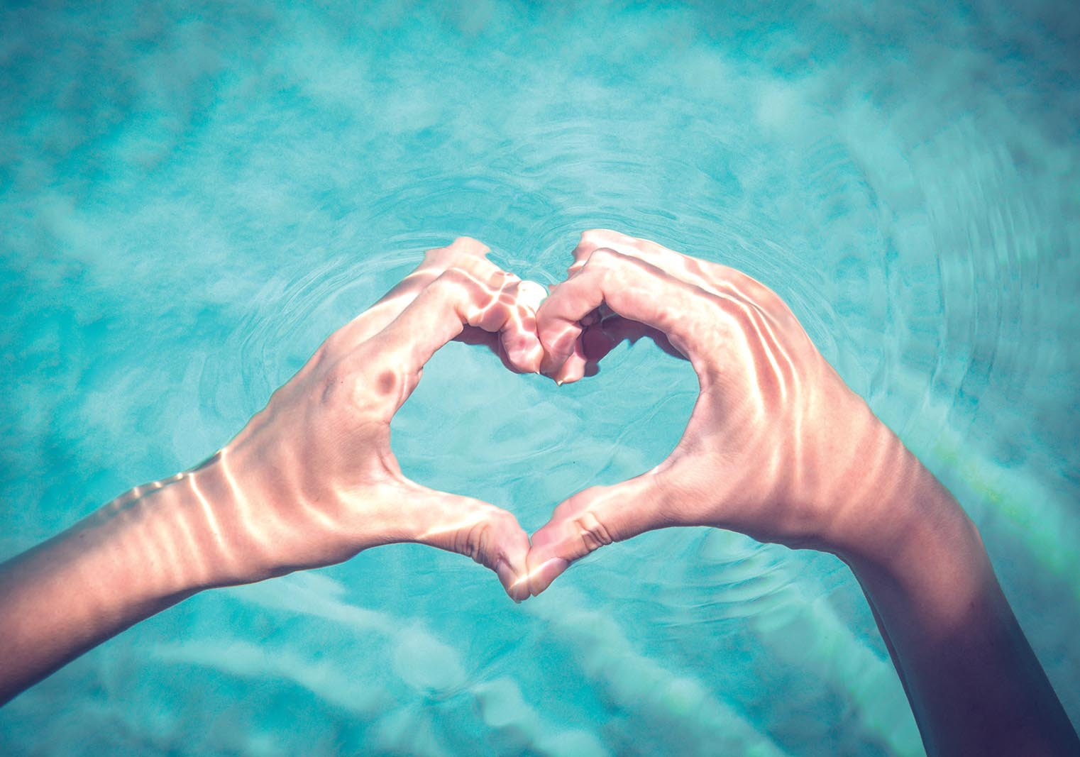 Hands in the shape of a heart over a pool | Bayberry at The Groves in Whittier, CA | Brookfield Residential