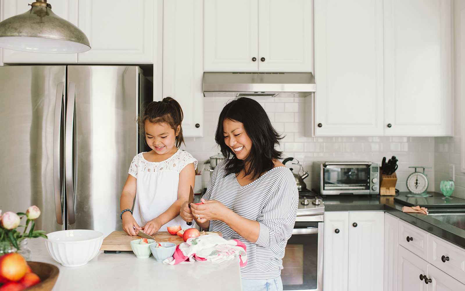 Mother and young daughter in the kitchen, cooking together while smiling