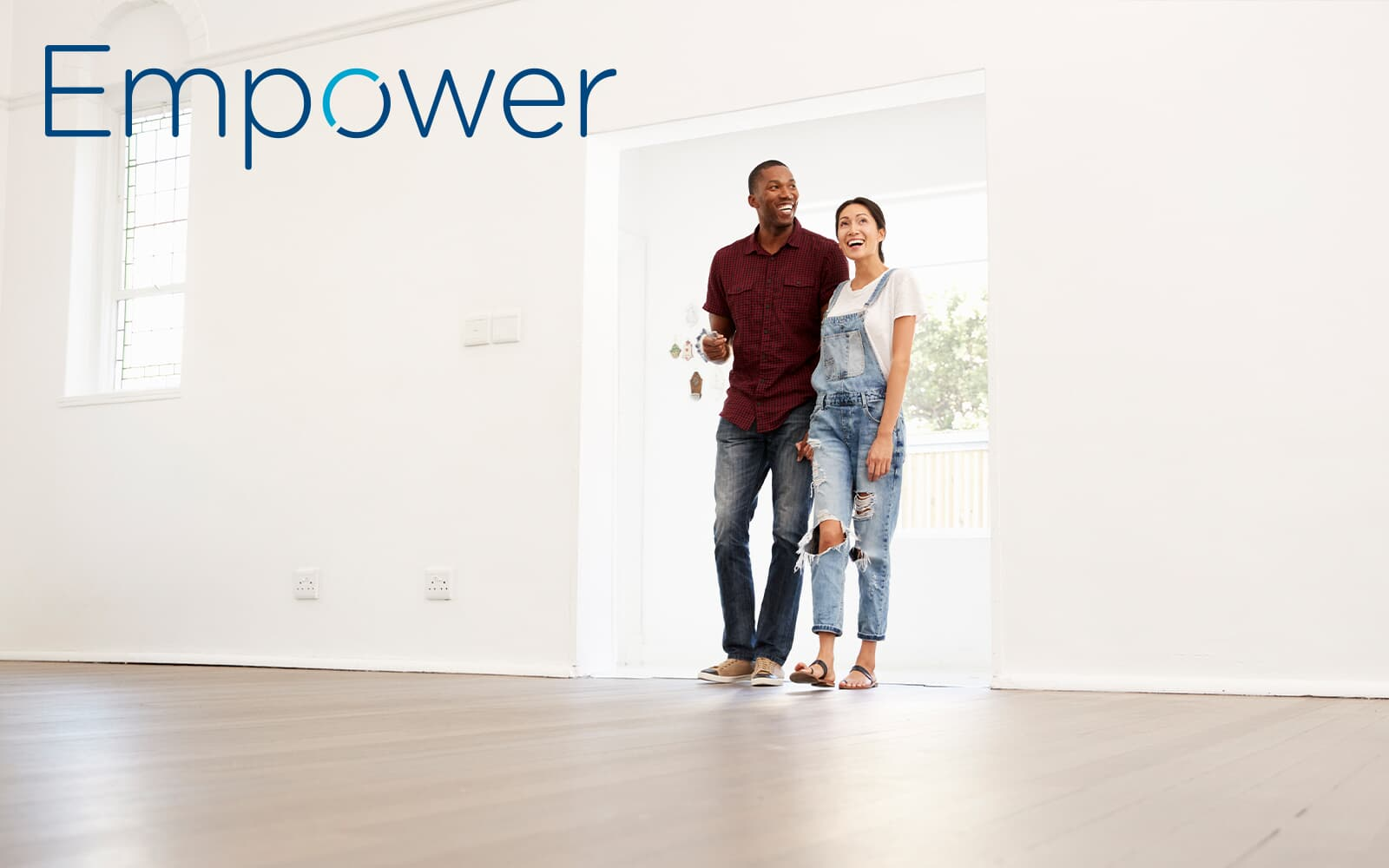 Empower logo over an image of a young couple standing in an open room of a new home